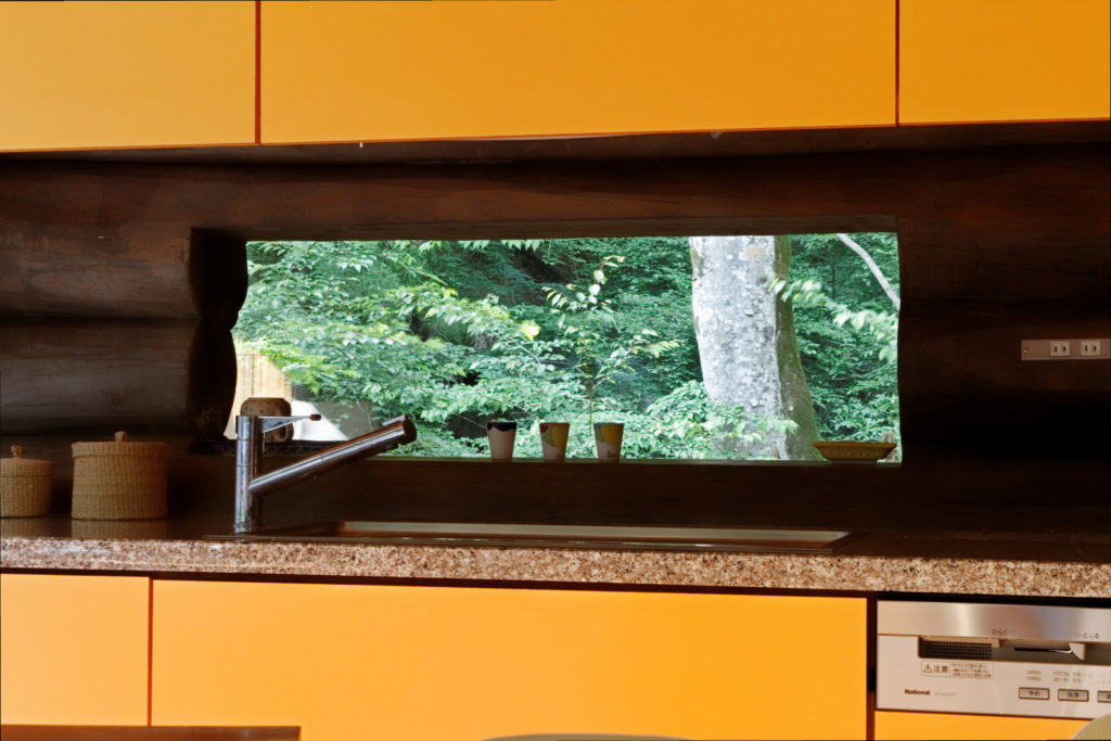 オレンジ色のキッチンと渓流の木々の緑