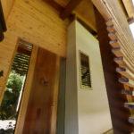 木製ルーバーと漆黒の丸太を抜けると木製の玄関ドアへ